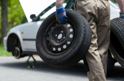Picture of a man holding two tires walking toward a vehicle that is hoisted up with no tires on it.